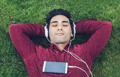 man with earbuds, relaxing on grass