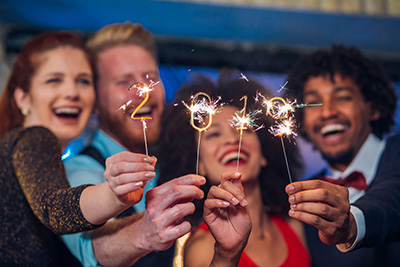 people celebrating New Years Eve with sparklers