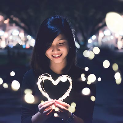 Woman smiling and holding an illuminated heart