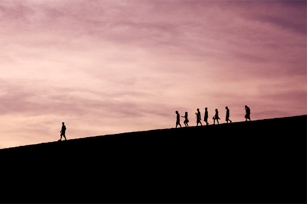 people walking against sunset