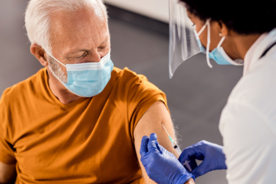 man getting injection from health professional